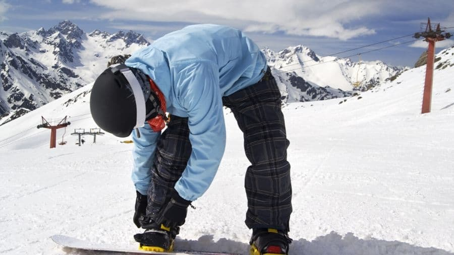 Snowboarder tightening up his snowboard bindings