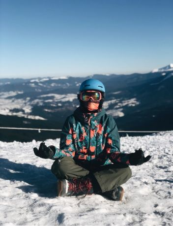 Snowboarder meditating on a snowy mountain
