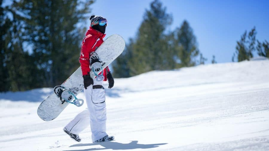 Snowboarder carrying a snowboard up a white snowy mountain