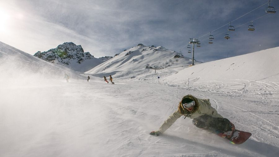 Cool snowboarder dude, snowboarding down a mountain at high speed
