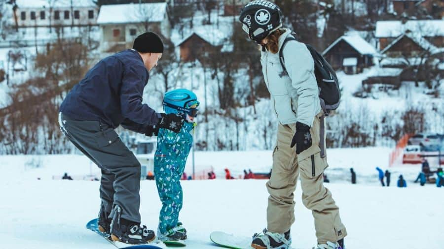 Mum and Dad teaching their kid to snowboard